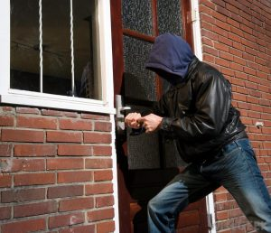 man-in-jeans-breaking-into-persons-brick-home